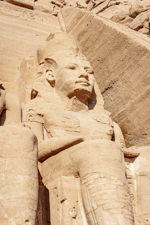 Den Abu Simbel UNESCOplatsen vaggar den sned statyn av Ramesses II eller Ramsses det stort nära den Abu Simbel byn Egypten arkivfoton