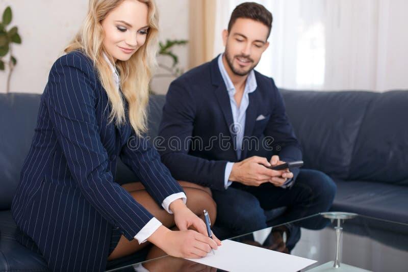 Den affärskvinnan och affärsmannen beräknar royaltyfri bild