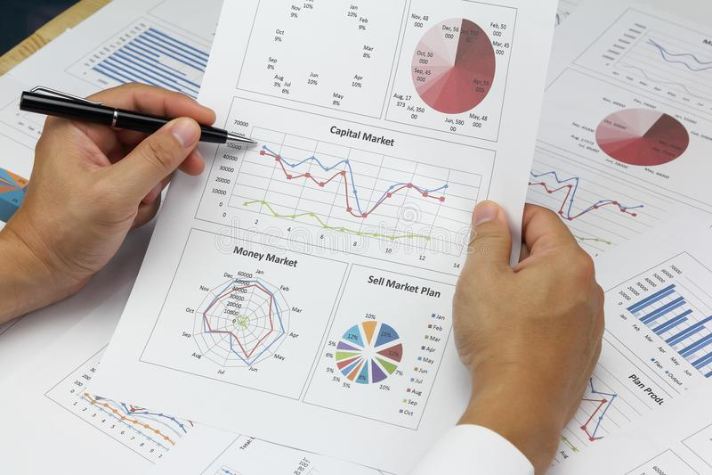 Den affärsmanSummary rapporten och kapitalmarknaden planerar analysering av ord arkivfoton