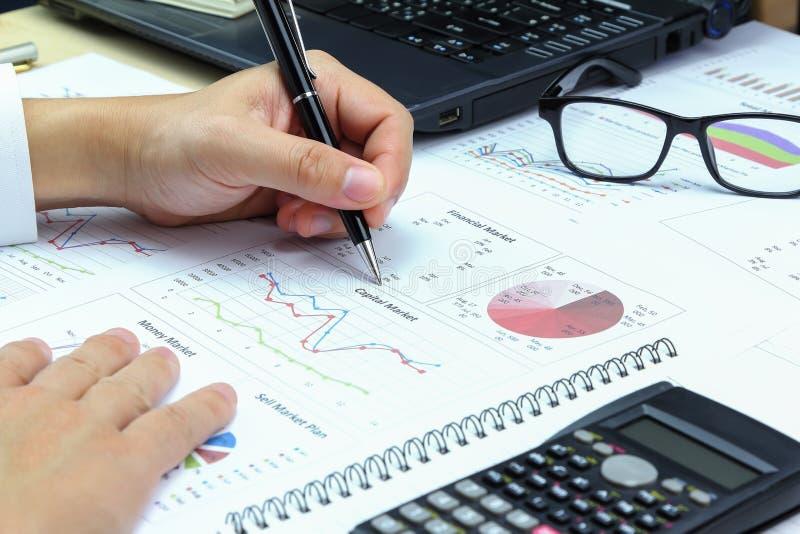 Den affärsmanSummary rapporten och kapitalmarknaden planerar analysering av ord arkivfoto