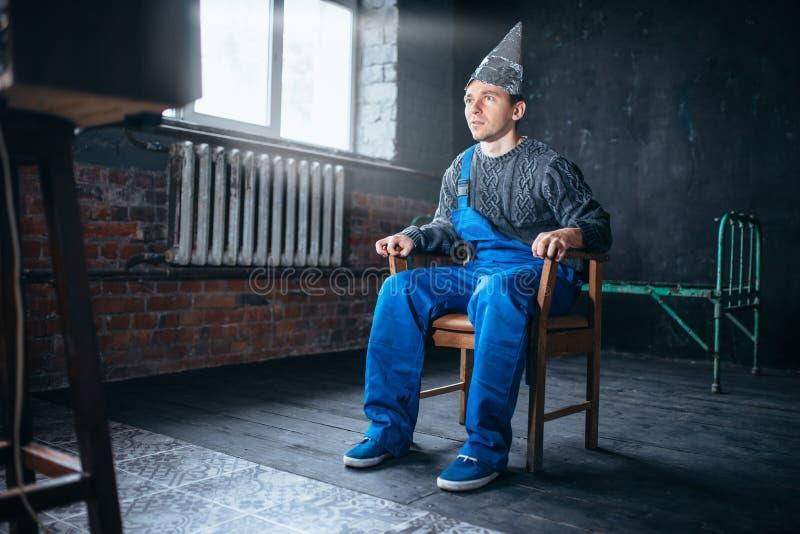 Den Afraided mannen i hjälm för aluminum folie sitter i stol royaltyfria foton