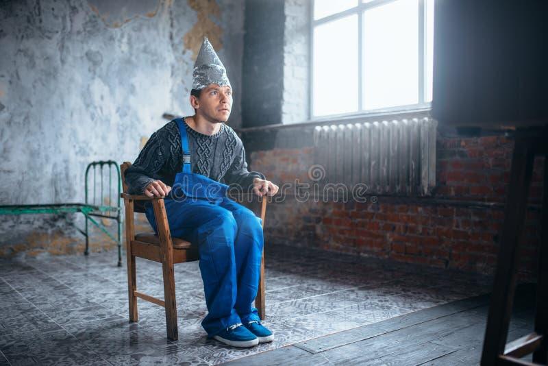 Den Afraided mannen i hjälm för aluminum folie sitter i stol arkivbilder