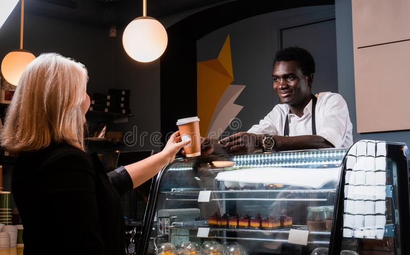 Den afrikanska baristaen ger den beställde kaffekunden av den moderna coffee shop royaltyfri foto