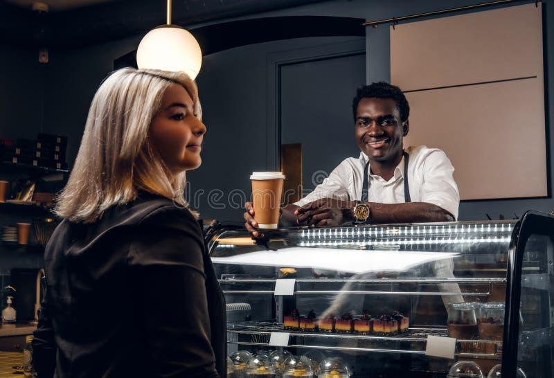 Den afrikanska baristaen ger den beställde kaffekunden av den moderna coffee shop royaltyfria foton