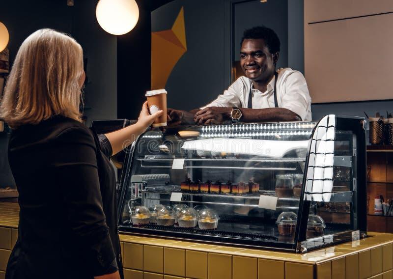 Den afrikanska baristaen ger den beställde kaffekunden av den moderna coffee shop fotografering för bildbyråer