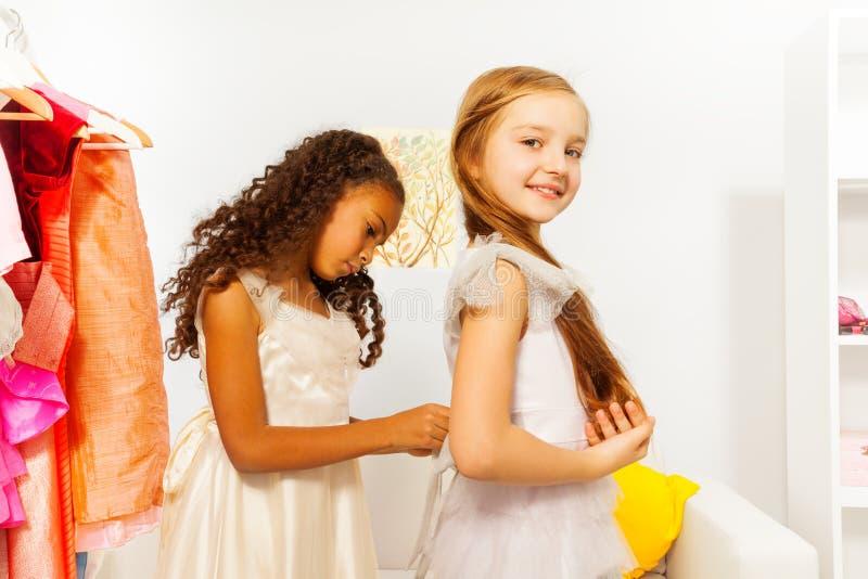 Den afrikanska flickan hjälper ett annat för att passa den vita klänningen arkivfoto