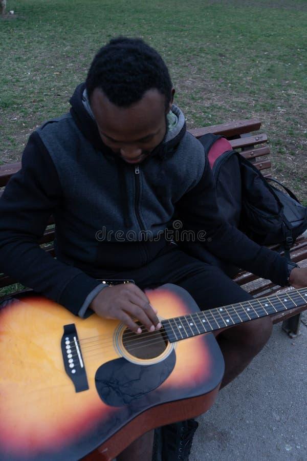 Den afrikanska grabben med en akustisk gitarr i en resväska som får klar att spela i, parkerar arkivfoto