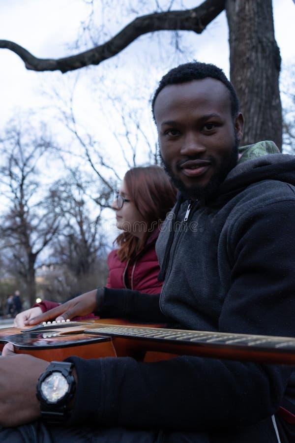 Den afrikanska grabben med en akustisk gitarr och en vit flicka med exponeringsglas i parkerar royaltyfri bild