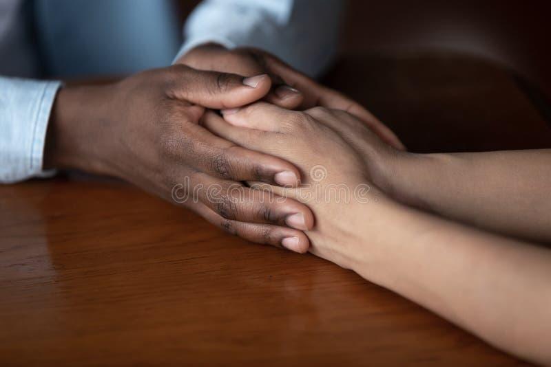 Den afrikanska grabben rymmer handen av det älskade flickaslutet upp bild royaltyfri bild
