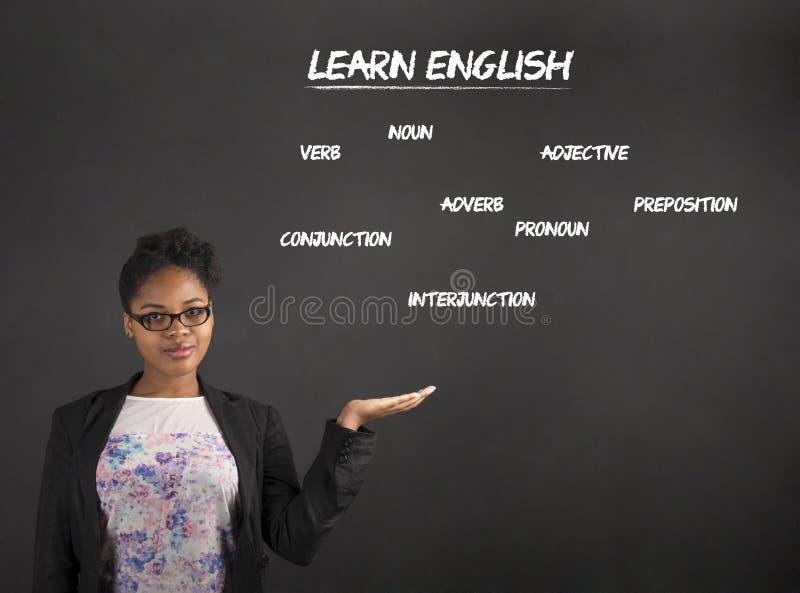 Den afrikanska kvinnainnehavhanden ut med lär engelska på svart tavlabakgrund royaltyfria foton