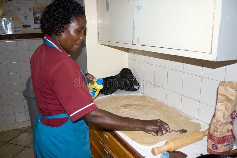Den afrikanska kvinnan förbereder chapatien arkivfoto