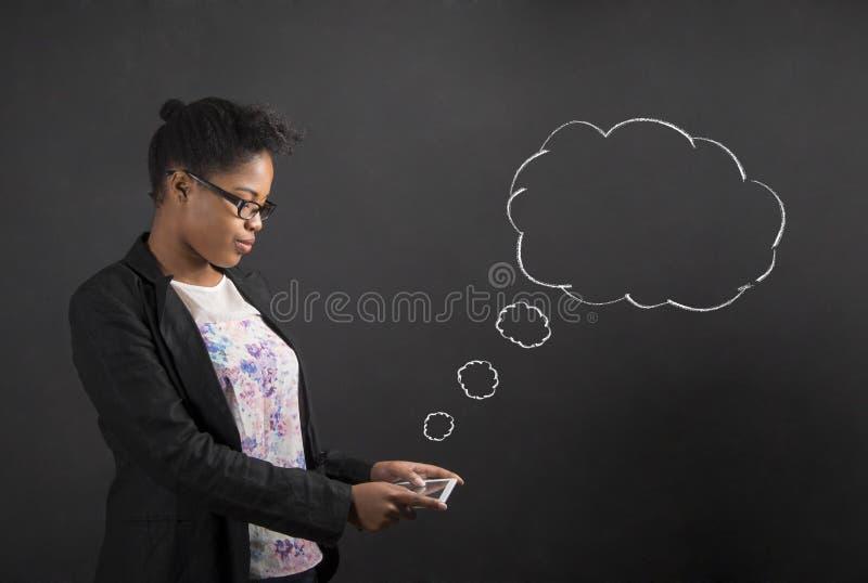 Den afrikanska kvinnan med minnestavlan och anförande eller tanke fördunklar på svart tavlabakgrund arkivbilder