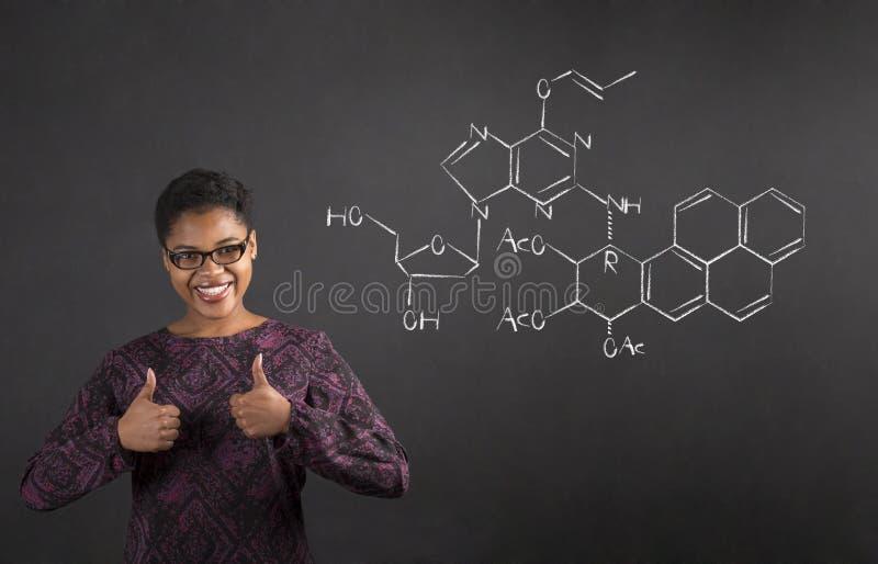 Den afrikanska kvinnan med tummar up handsignalen med vetenskap på svart tavlabakgrund royaltyfri fotografi