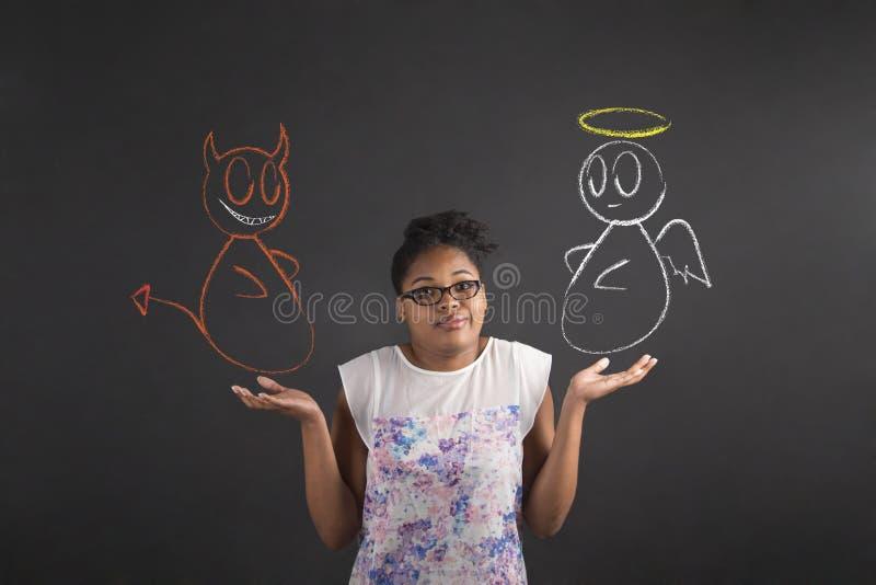 Den afrikanska kvinnan med vet jag inte ängel- och jäkelgest på svart tavlabakgrund royaltyfri foto