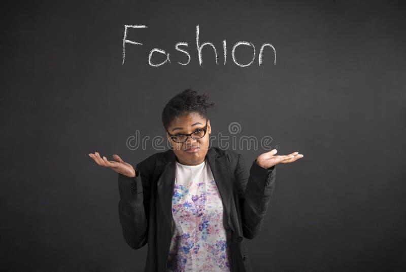 Den afrikanska kvinnan med vet jag inte om modegest på svart tavlabakgrund arkivfoto