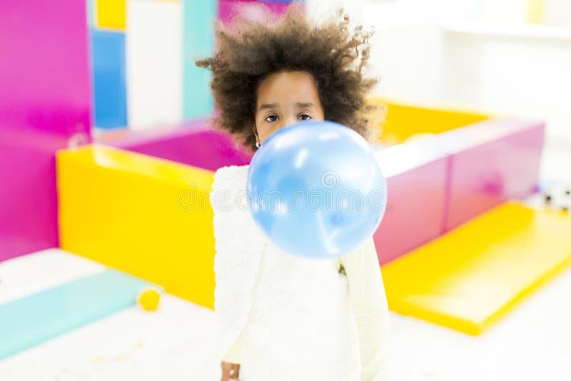 Den afrikanska lilla flickan blåser upp blåttballongen fotografering för bildbyråer