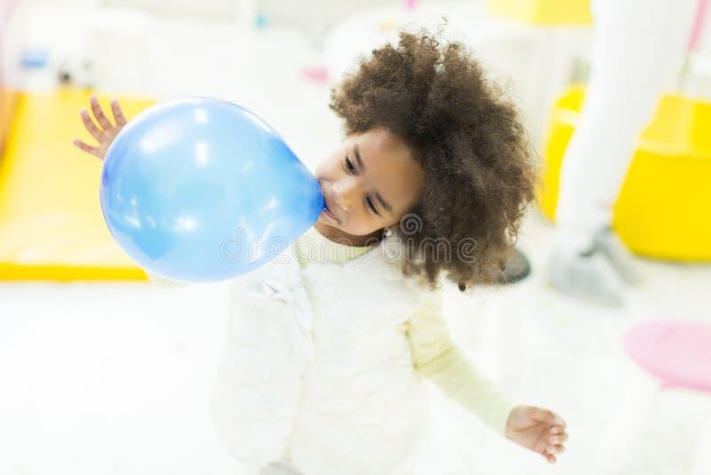Den afrikanska lilla flickan blåser upp blåttballongen arkivbilder