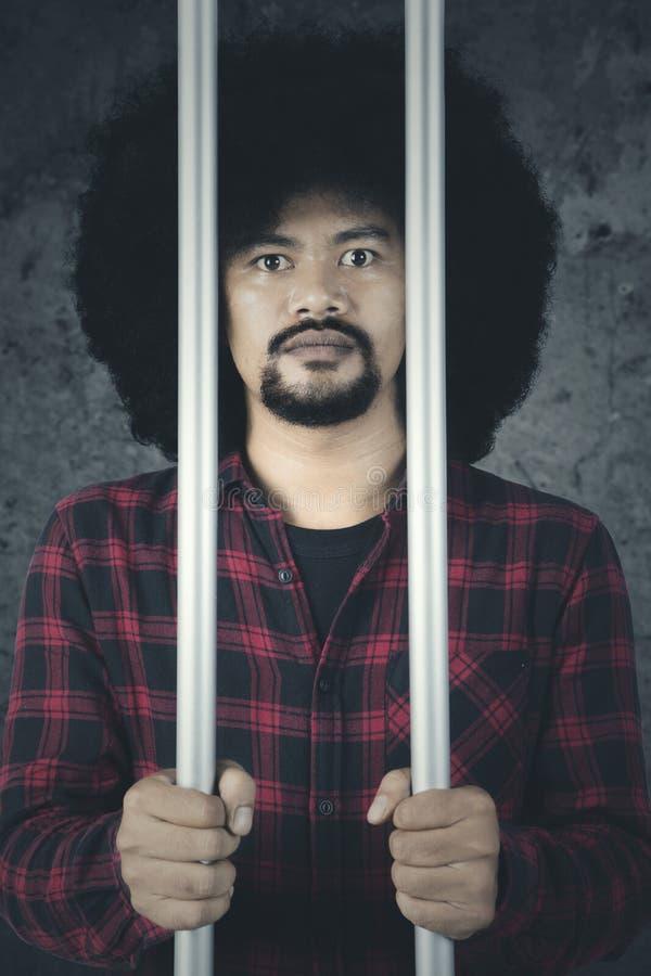 Den afrikanska mannen är bak ett fängelse royaltyfria foton