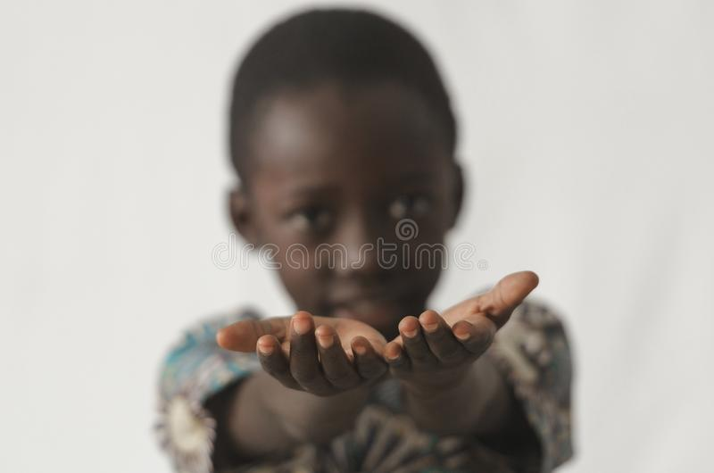 Den afrikanska pojken som rymmer hans händer, öppnar som ett begrepp som isoleras på whi fotografering för bildbyråer