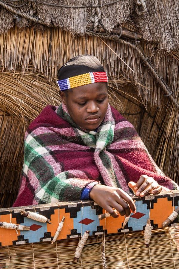 Den afrikanska zulu- kvinnan väver sugrörmatta royaltyfri bild