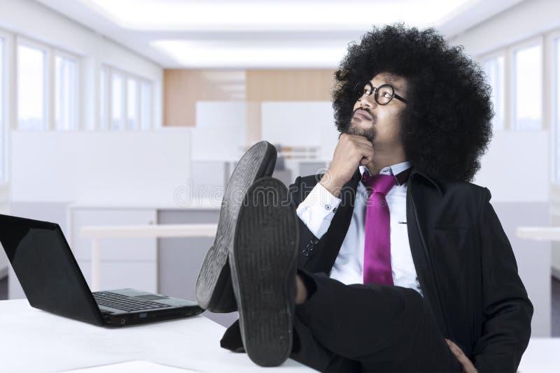 Den afro- affärsmannen ser eftertänksam i arbetsplatsen royaltyfria bilder