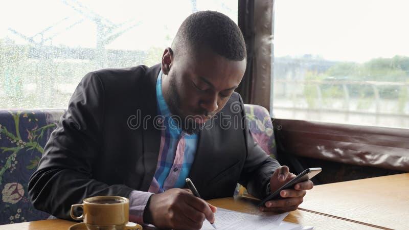Den afro- amerikanska affärsmannen fyller documets i sommartältkafét som ser i smartphone royaltyfri bild
