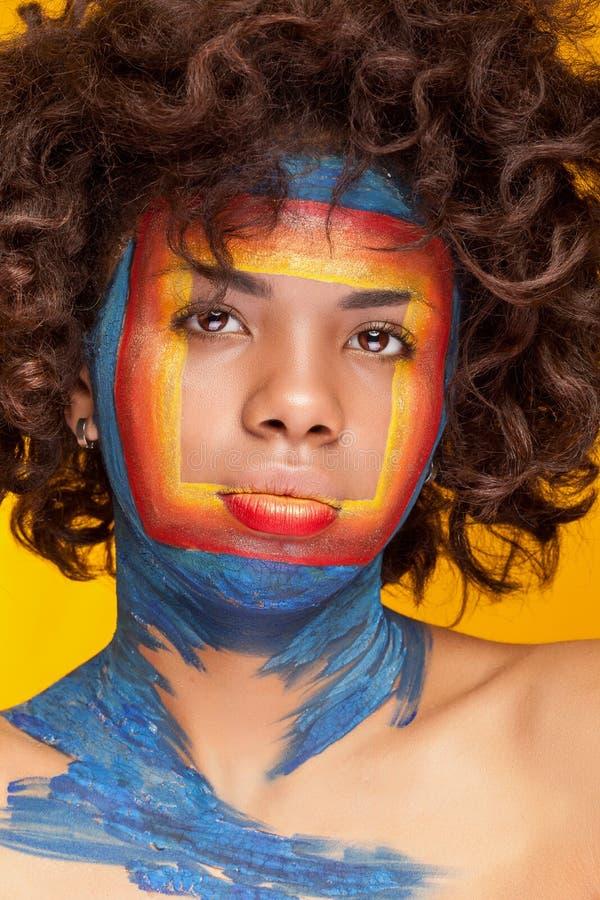 Den afro- amerikanska flickan på gul bakgrund med skönhetfyrkanten gör royaltyfria bilder