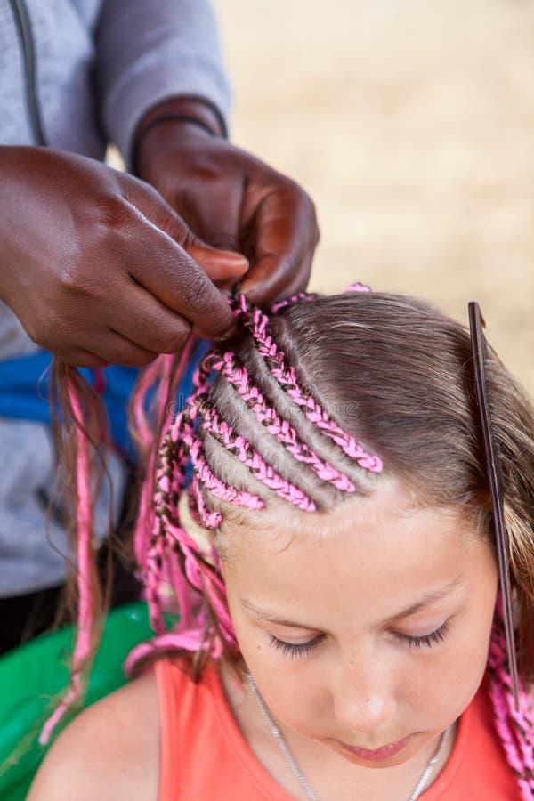 Den afro- amerikanska frisören gjorde tunna rosa flätor i afrikansk stil för ung Caucasian flicka royaltyfria foton