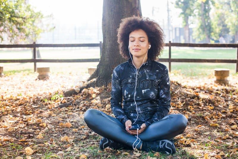 Den afro- unga kvinnan kopplar av och lyssnande musik efter utbildning royaltyfri fotografi