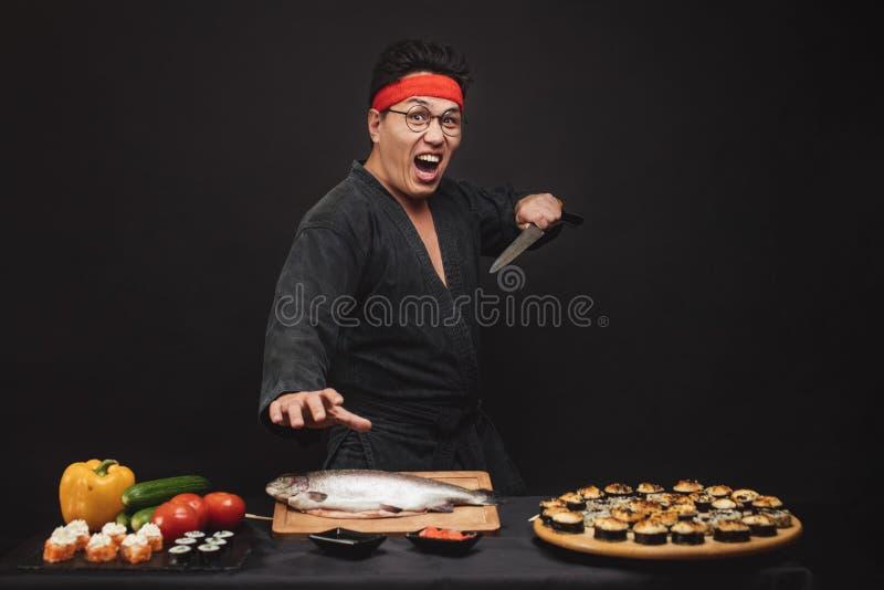 Den aggressiva mannen i kimono lagar mat sushi arkivfoto