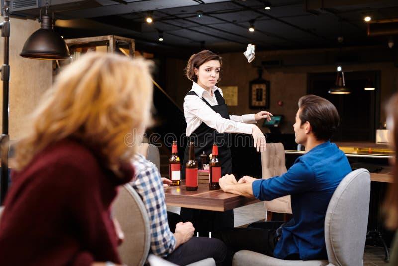 Den aggressiva servitrins som kastar pengar i gäster, vänder mot royaltyfri fotografi