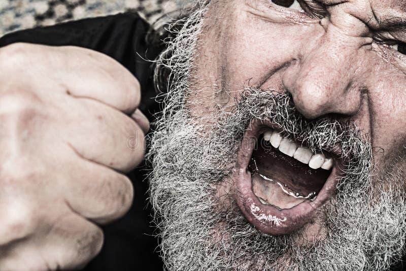 Den aggressiva skriande mannen med en gripen hårt om näve, öppnar munnen och gre royaltyfri fotografi