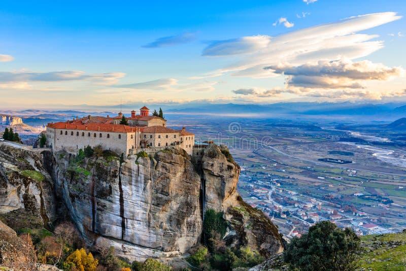 Den Agios Stephanos eller St Stephen kloster som lokaliseras på det enormt, vaggar med berg och stadlandskapet i bakgrunden, mete arkivbild