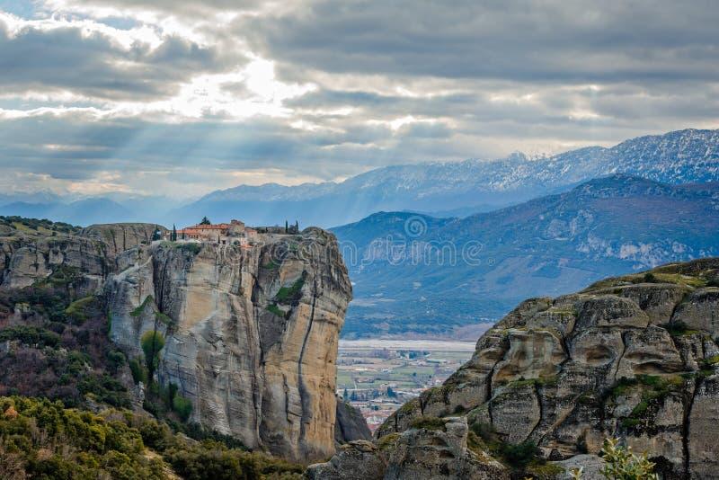Den Agios Stephanos eller St Stephen kloster som placeras på det enormt, vaggar med solnedgångstrålar och berg i bakgrunden, mete royaltyfria foton