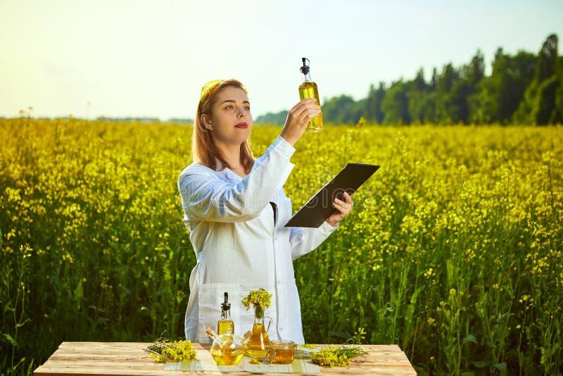 Den agronomkvinnan eller bonden undersöker rapsolja som använder minnestavlan på bakgrunden av att blomstra, våldtar canolafältet royaltyfri fotografi