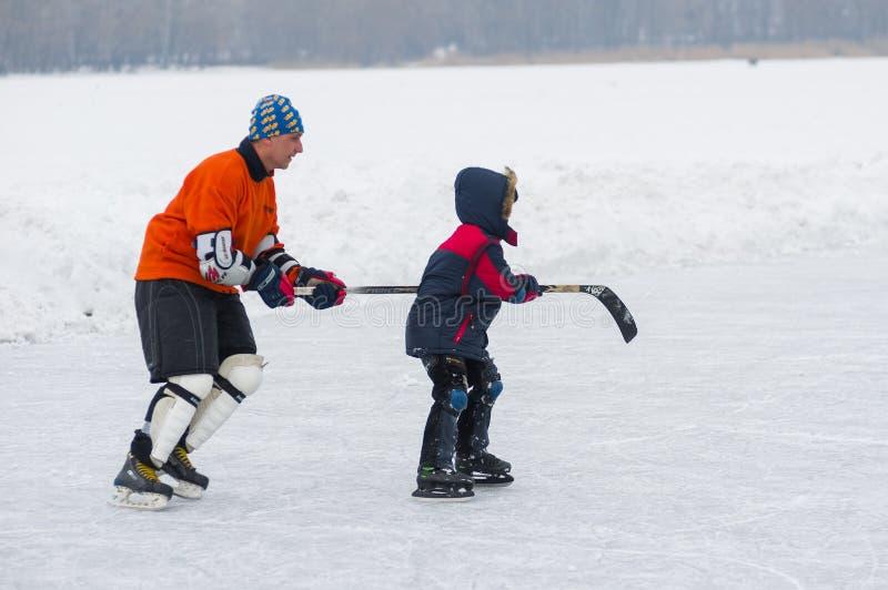 Den aktiva fadern undervisar sonen att åka skridskor royaltyfria foton