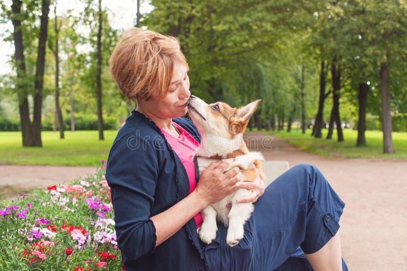Den aktiva höga kvinnan med hunden på går i en härlig sommarnatur royaltyfri foto