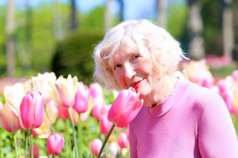 Den aktiva höga kvinnan som tycker om blommor, parkerar arkivbild