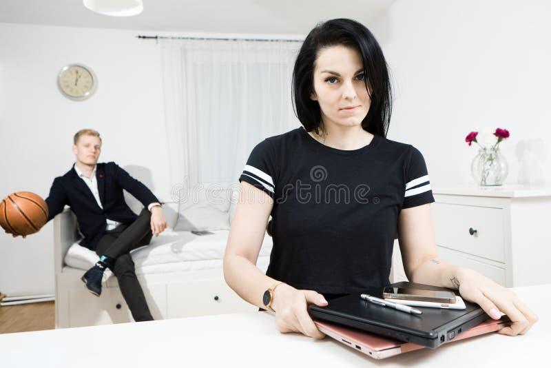 Den aktiva kvinnan avslutade arbete på skrivbordet och den eleganta mannen som väntar i bakgrunden arkivbild