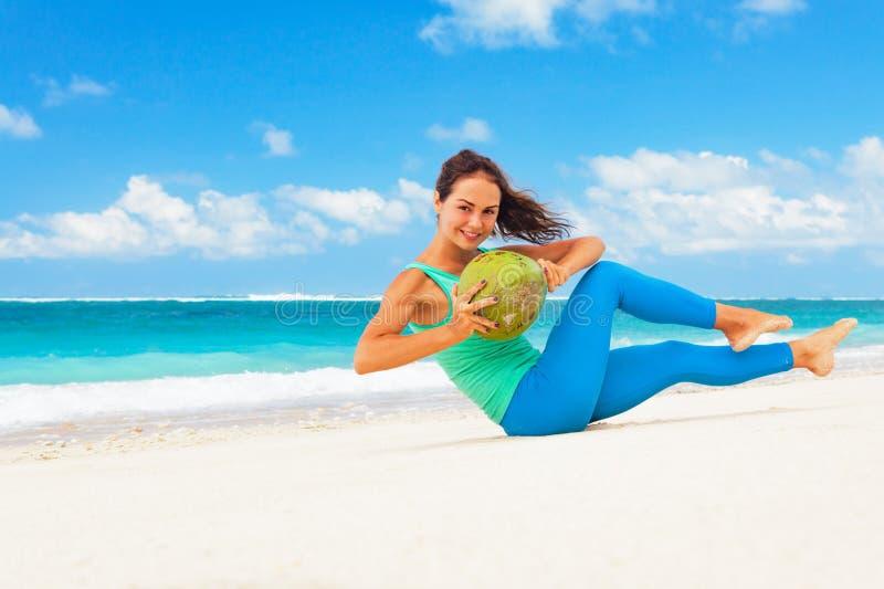Den aktiva kvinnan som gör sportar, övar med kokosnötter på havsstranden royaltyfria foton