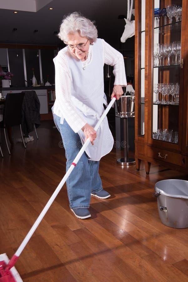 Den aktiva kvinnliga pensionären gör ren golvet royaltyfri bild