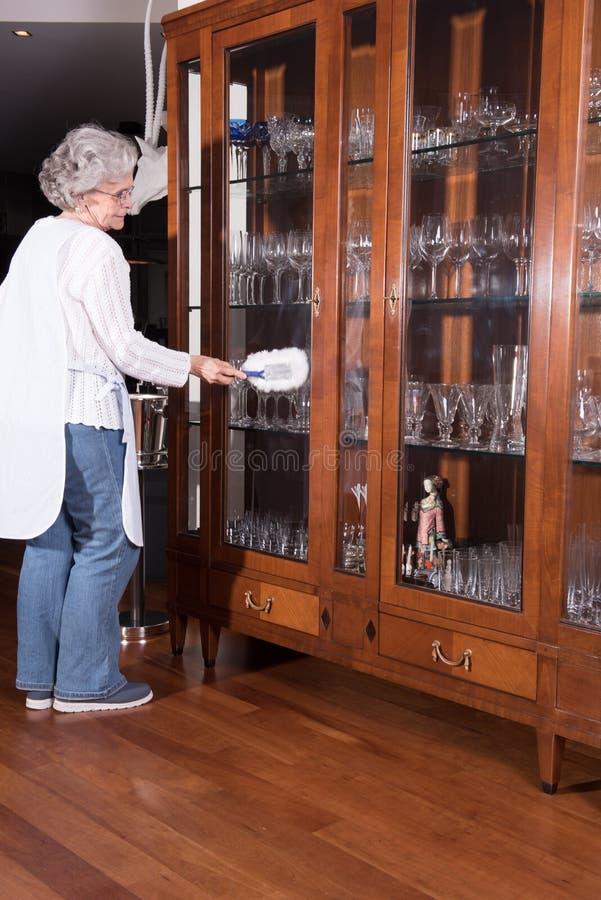 Den aktiva kvinnliga pensionären gör ren möblemang royaltyfria bilder
