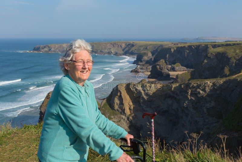 Den aktiva lyckliga äldre kvinnliga pensionären i eighties med rörlighetsramen och att gå är lojal mot härlig kustplats royaltyfri fotografi