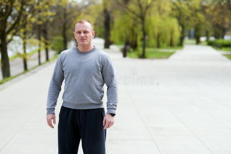 Den aktiva mannen med den idrotts- kroppen, övar utomhus- parkerar in Färdig blick fotografering för bildbyråer