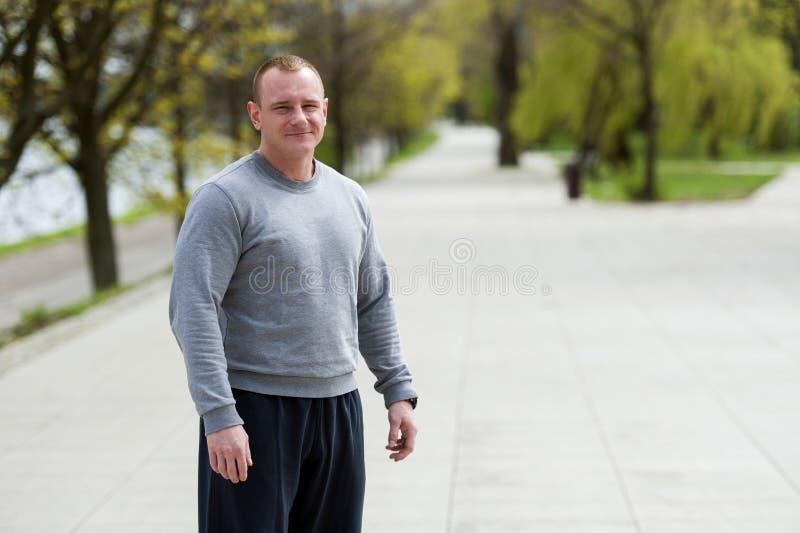 Den aktiva mannen med den idrotts- kroppen, övningsoutdoore parkerar in Färdig blick royaltyfri fotografi