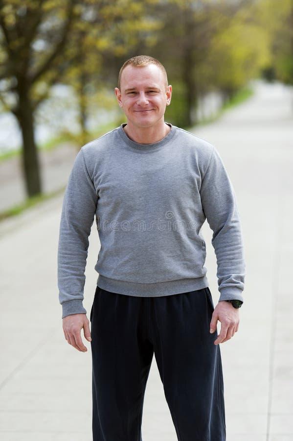 Den aktiva mannen med den idrotts- kroppen, övningsoutdoore parkerar in Färdig blick arkivbilder