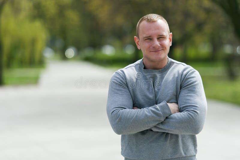 Den aktiva mannen med den idrotts- kroppen och korsade armar, övar utomhus- arkivfoton