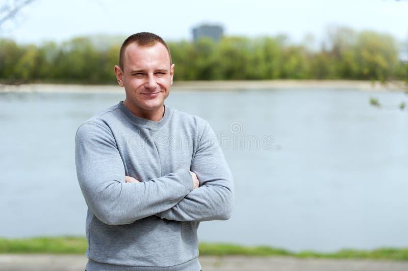Den aktiva mannen med den idrotts- kroppen och korsade armar, övar utomhus- royaltyfri foto