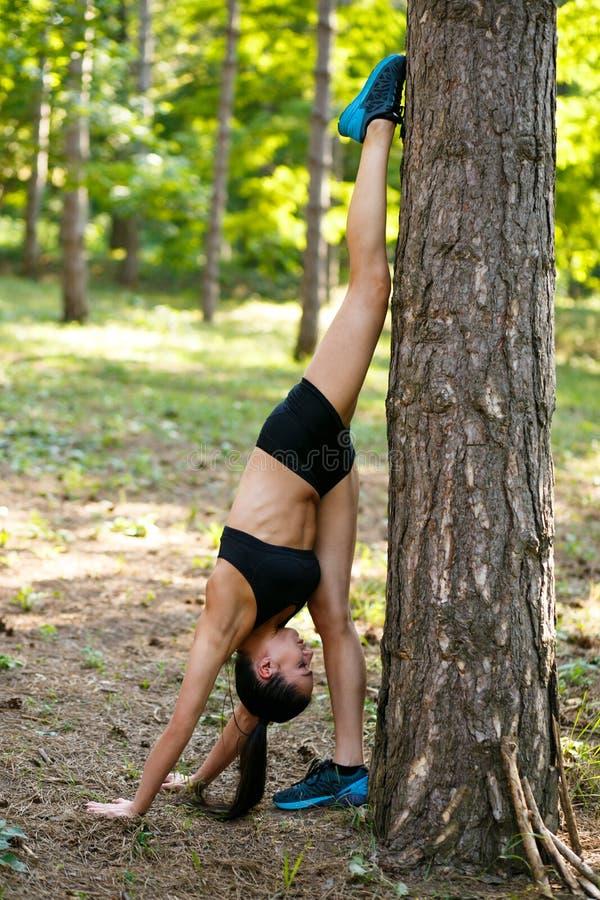 Den aktiva unga brunettkvinnan som gör styrkaövningar med ben upp ett huvud ner nära träd parkerar in, i sommartid royaltyfria bilder