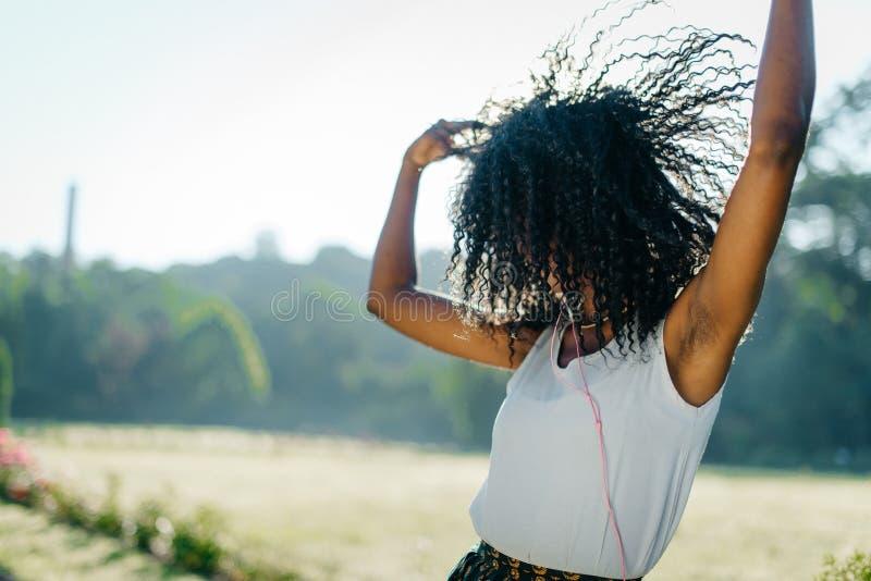 Den aktiva unga nätta afrikanska flickan är dansa och skaka emotionaly hennes mörka lockiga hår, medan lyssna till musik i henne royaltyfri fotografi